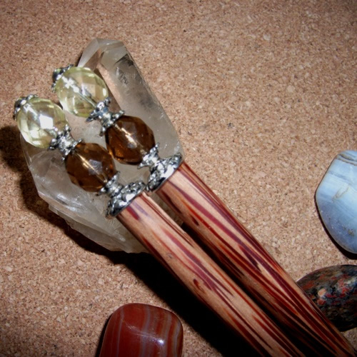 A pair ofCoconut hairsticks with Topaz and lemon crystals handmade by Longhaired Jewels